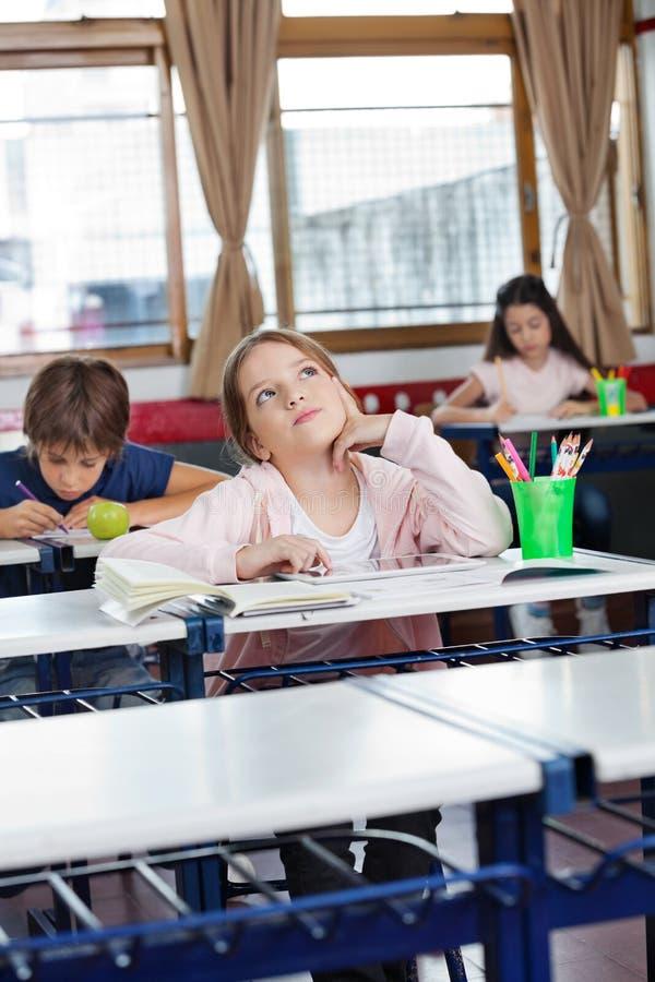 Écolière regardant avec la Tablette de Digital le bureau photo libre de droits