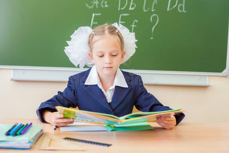 Écolière s'asseyant au bureau, à la salle de classe d'école, et au livre de lecture photo stock