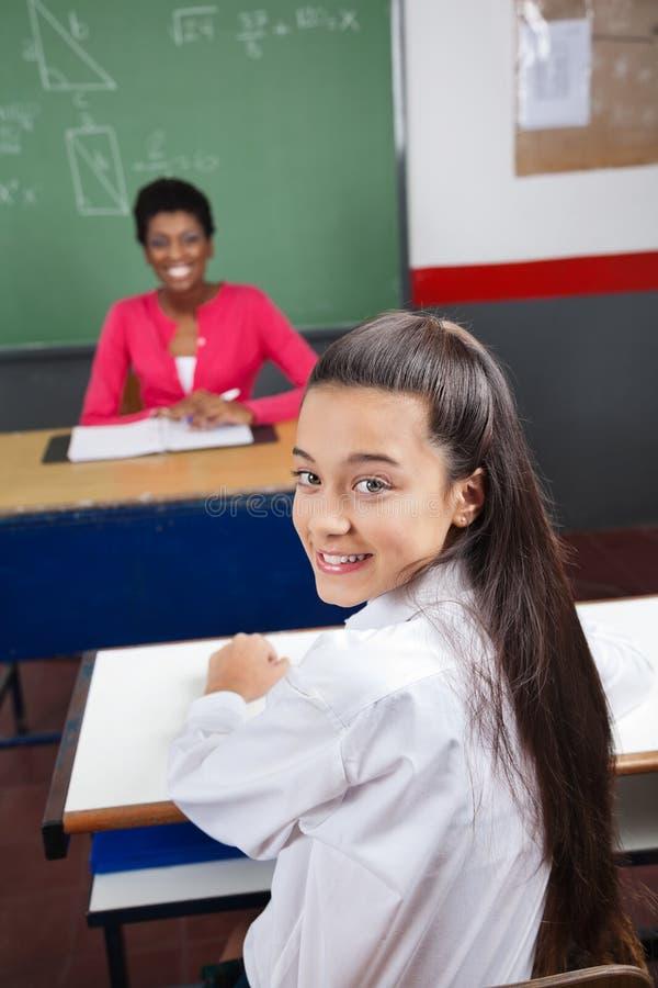 Écolière s'asseyant au bureau avec le professeur Smiling In photographie stock libre de droits