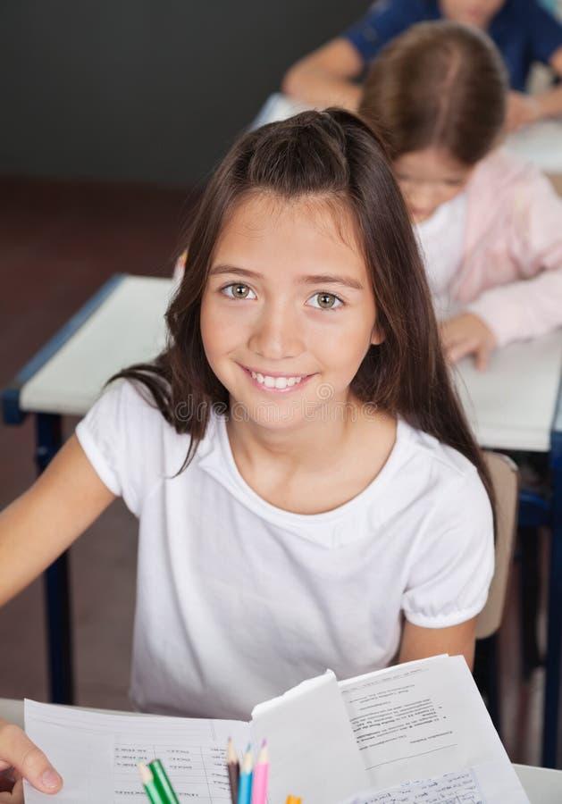 Écolière s'asseyant au bureau dans la salle de classe photo stock