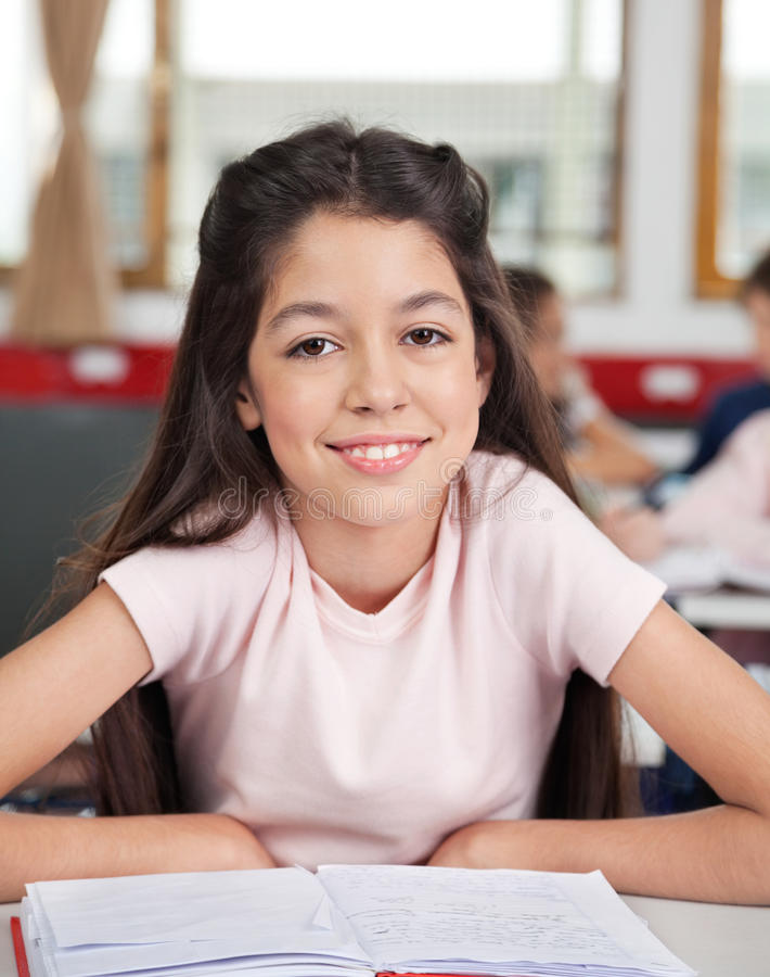 Écolière s'asseyant au bureau dans la salle de classe photo libre de droits