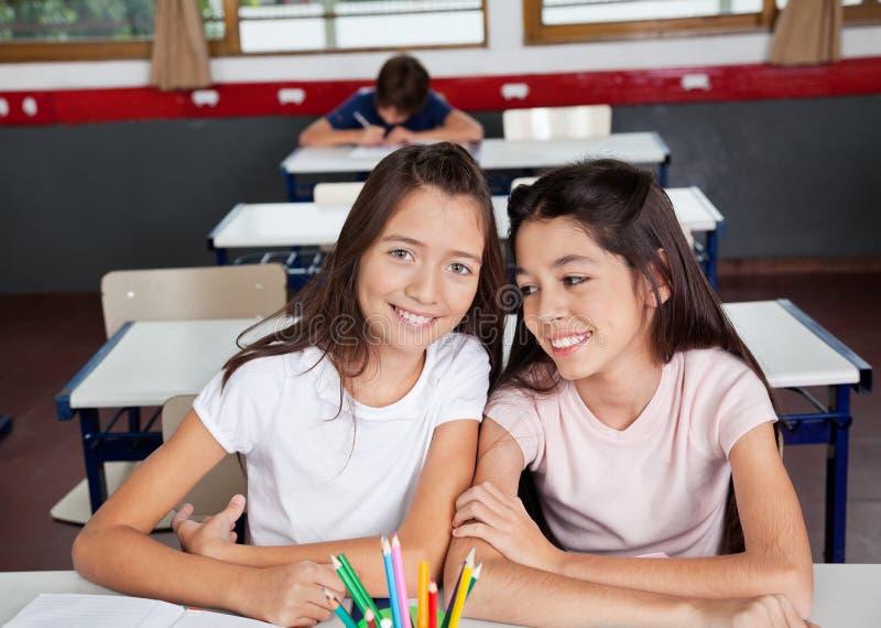 Écolière s'asseyant avec l'ami féminin dans la salle de classe photo stock