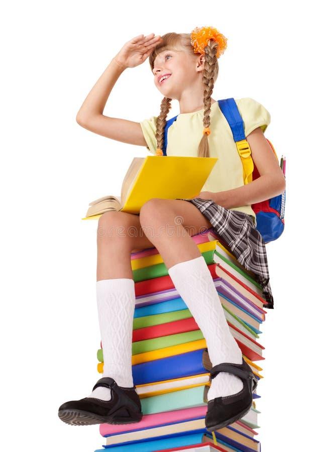 Écolière s'asseyant sur la pile des livres. image stock