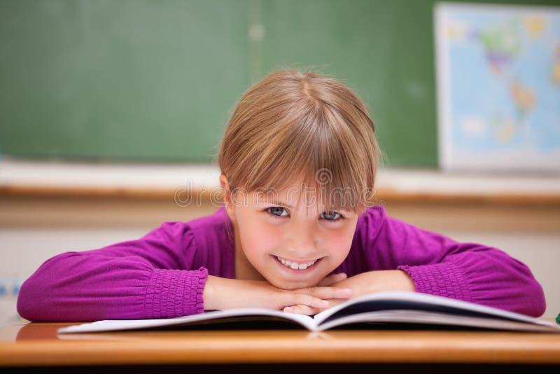 Écolière se penchant sur un bureau photo stock