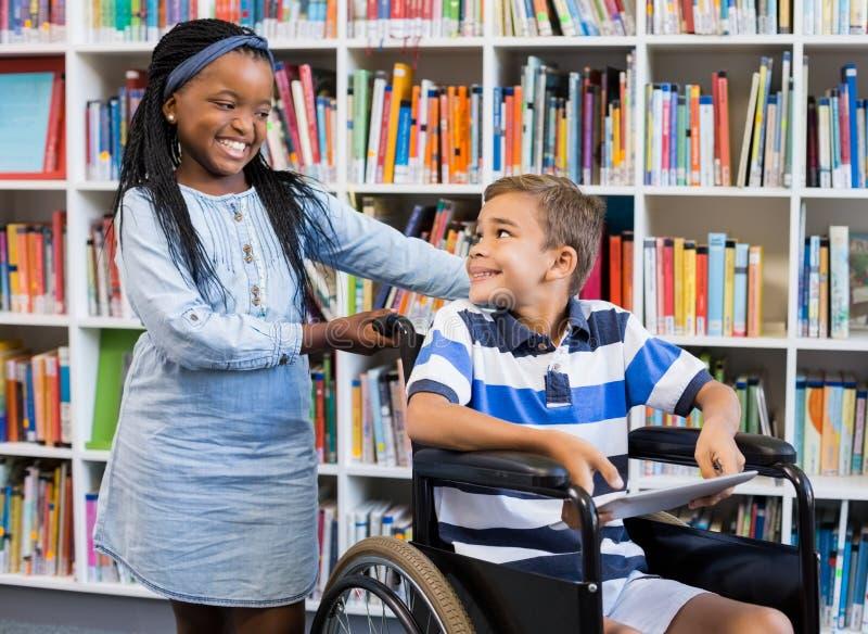 Écolière se tenant avec le garçon handicapé sur le fauteuil roulant photo stock