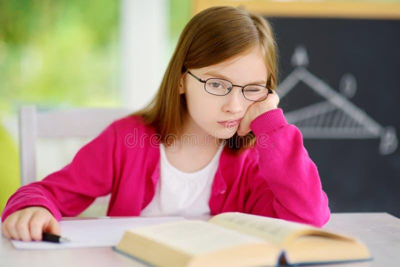 Écolière soumise à une contrainte et fatiguée étudiant avec une pile des livres sur son bureau image stock