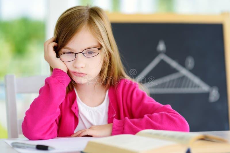 Écolière soumise à une contrainte et fatiguée étudiant avec une pile des livres sur son bureau photos stock