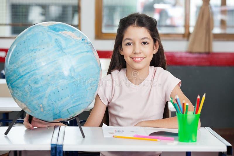 Écolière souriant avec le globe images stock