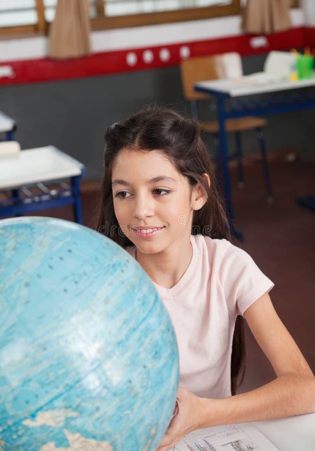 Écolière souriant tout en recherchant des endroits sur le globe photos stock