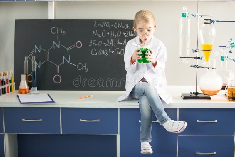 Écolière tenant le flacon avec l'échantillon chimique tout en se reposant images libres de droits