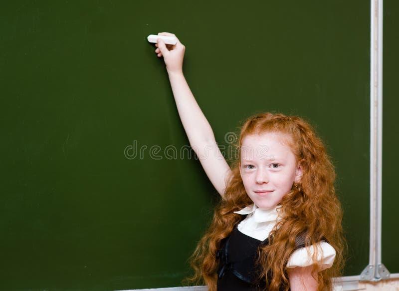 Écolière tenant une craie blanche environ pour écrire photographie stock libre de droits