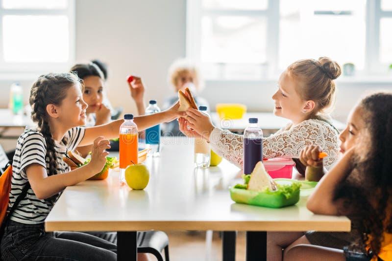 écolières adorables prenant le déjeuner images libres de droits