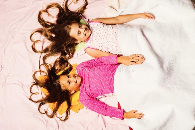 Écolières ayant la partie de pyjama tenant des mains Enfance et bonjour photos stock
