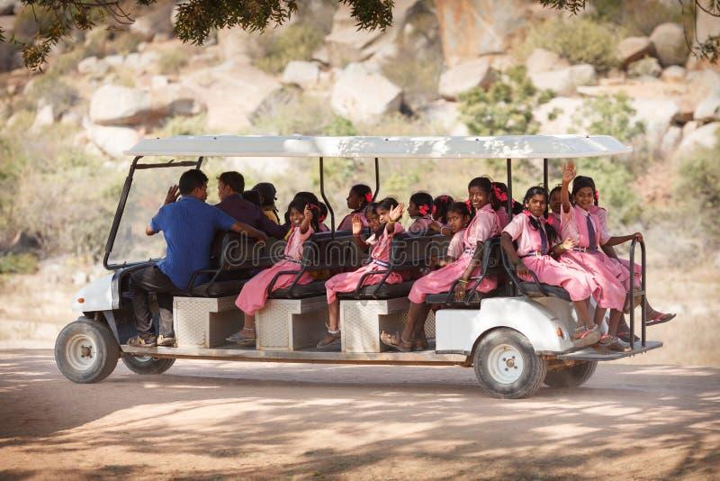 Écolières dans des robes roses, allant sur le long véhicule électrique photo libre de droits