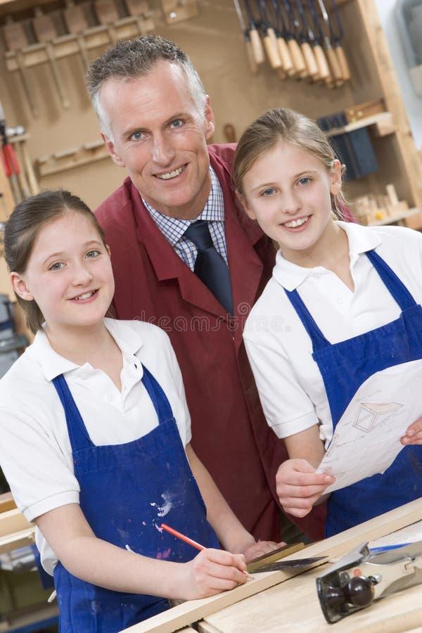 Écolières et professeur dans la classe de boisage photographie stock