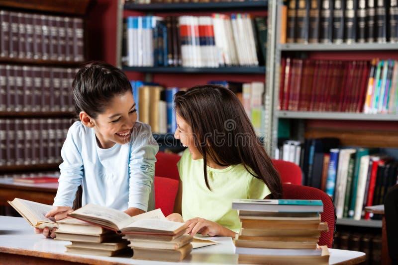 Écolières heureuses regardant l'un l'autre tandis que photos libres de droits