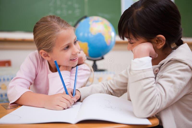 Écolières mignonnes faisant des devoirs photo stock