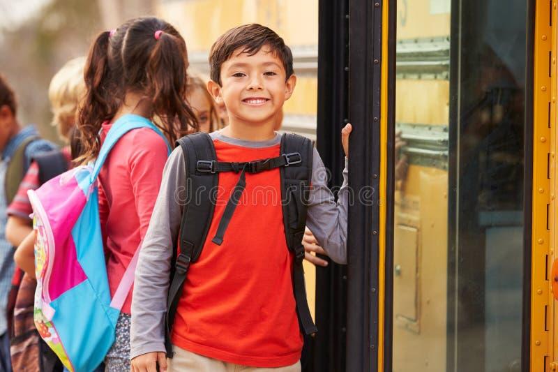 Écolier élémentaire à l'avant de la file d'attente d'autobus scolaire photos libres de droits