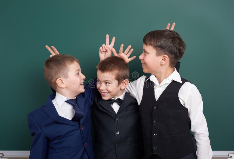 Écolier élémentaire dupant autour près du fond vide de tableau, habillé dans le costume noir classique, élève de groupe, conce d' image stock