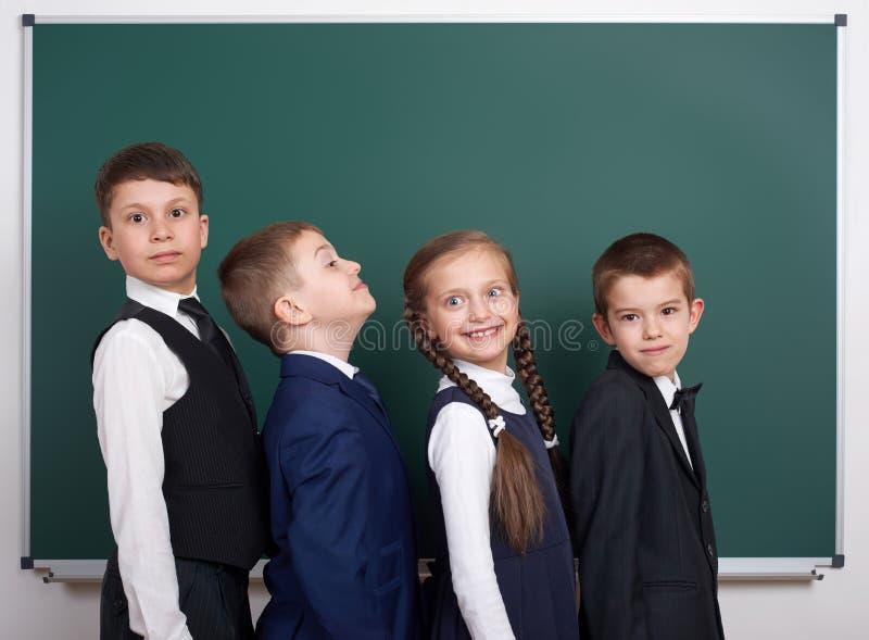 Écolier élémentaire près du fond vide de tableau, habillé dans le costume noir classique, élève de groupe, concept d'éducation photographie stock libre de droits