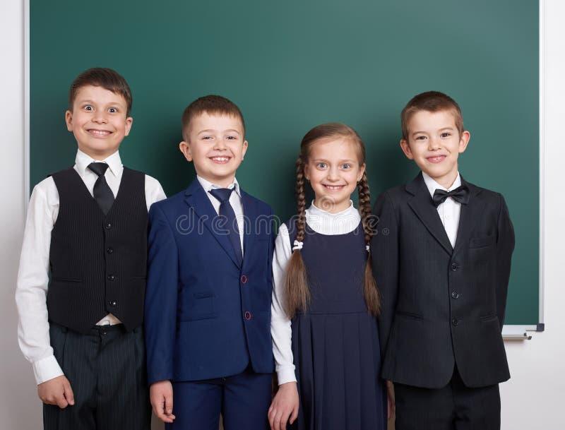 Écolier élémentaire près du fond vide de tableau, habillé dans le costume noir classique, élève de groupe, concept d'éducation photos libres de droits