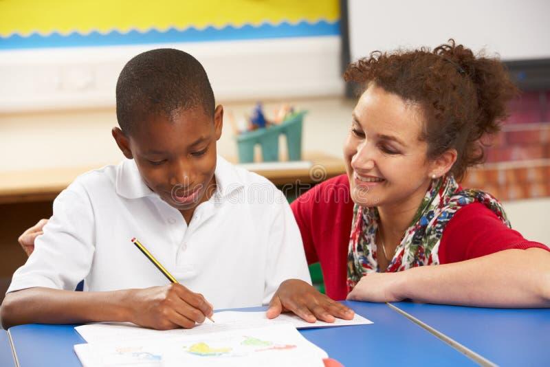 Écolier étudiant dans la salle de classe avec le professeur photographie stock libre de droits