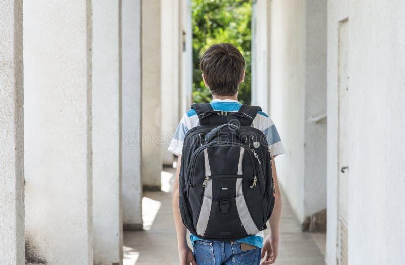 Écolier adolescent avec un sac à dos sur le sien dos marchant à l'école image libre de droits