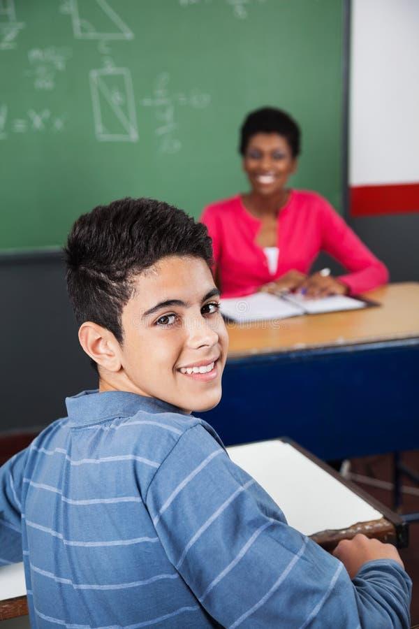 Écolier adolescent heureux s'asseyant au bureau photo stock