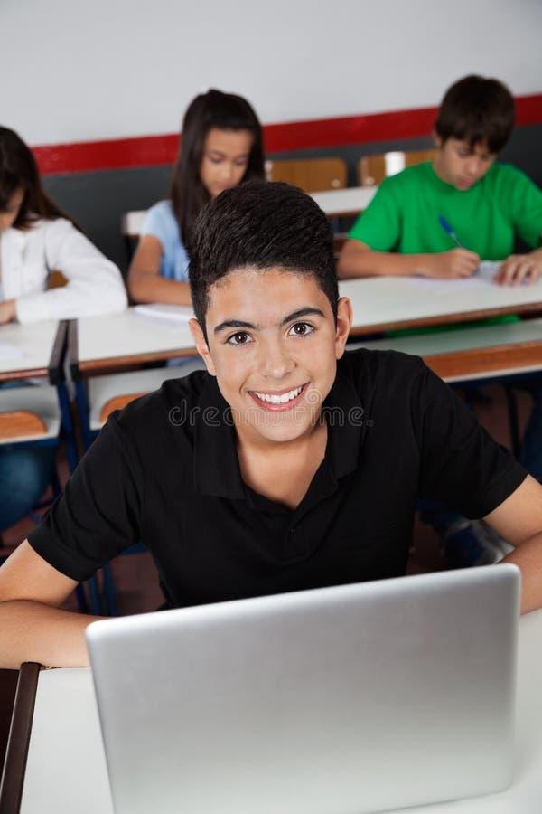 Écolier adolescent heureux s'asseyant avec l'ordinateur portable dedans photo libre de droits