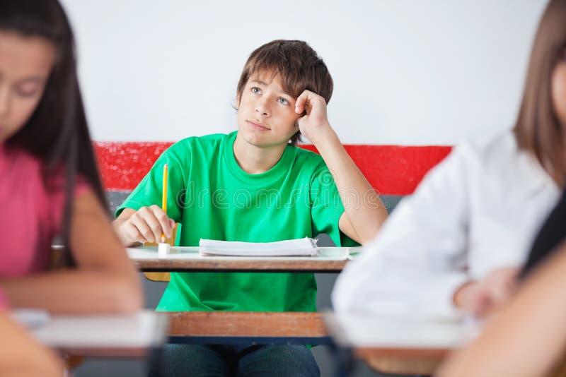 Écolier adolescent réfléchi s'asseyant au bureau image stock