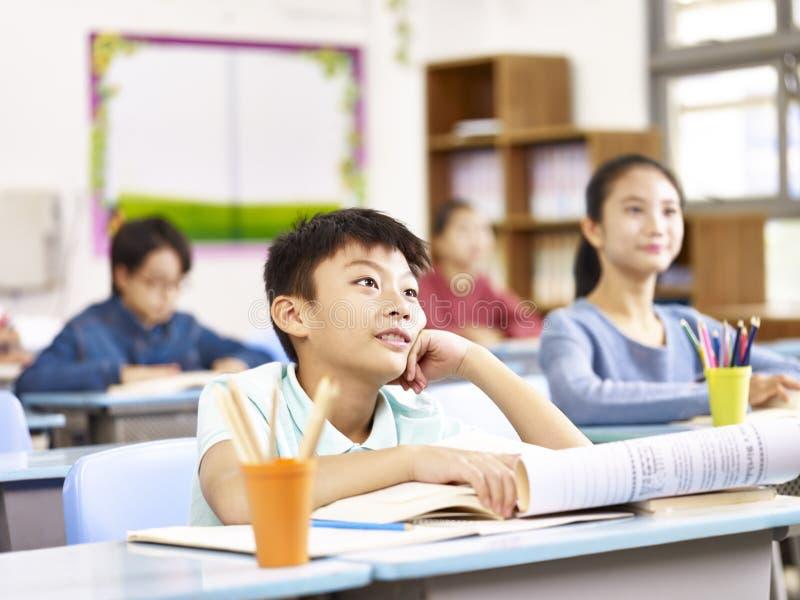 Écolier asiatique dans la classe photo stock