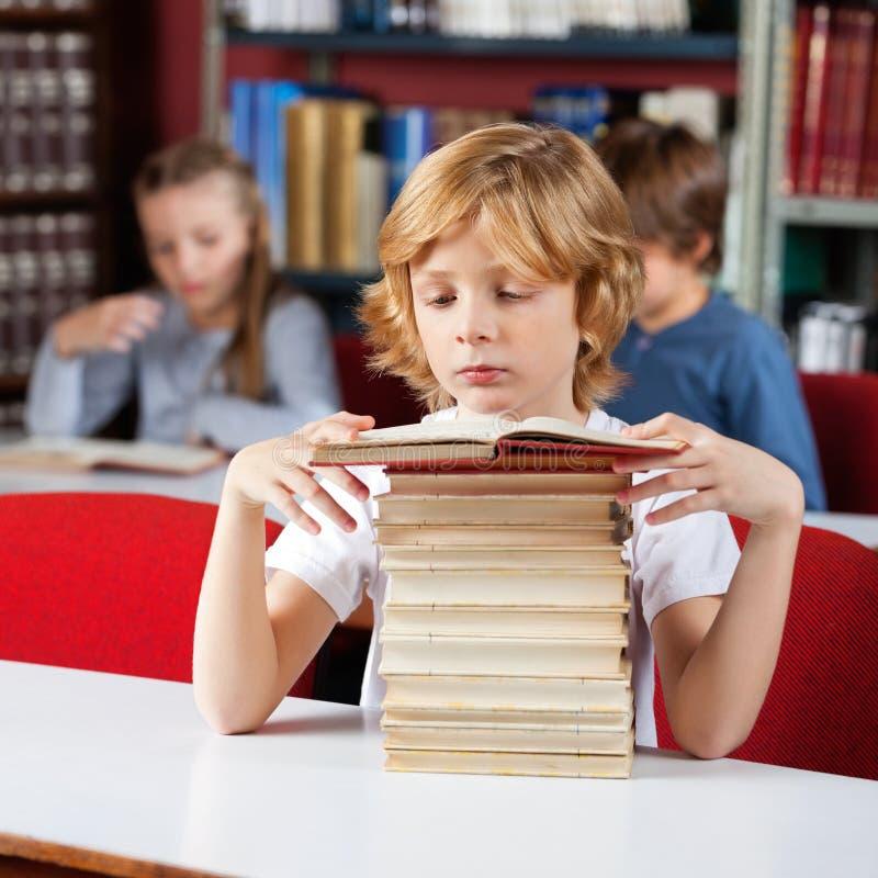 Écolier avec la pile de livres images stock