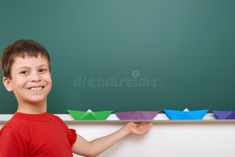 Écolier avec le jeu de papier de bateau près d'un tableau noir, l'espace vide, concept d'éducation photos libres de droits