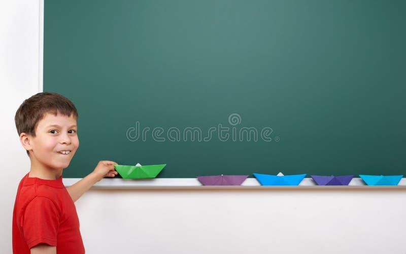 Écolier avec le jeu de papier de bateau près d'un tableau noir, l'espace vide, concept d'éducation images libres de droits
