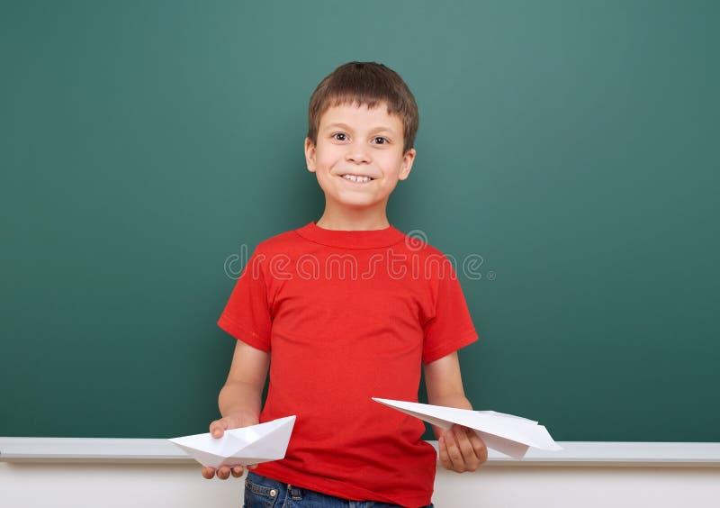 Écolier avec le jeu plat de papier près d'un tableau noir, l'espace vide, concept d'éducation photographie stock libre de droits