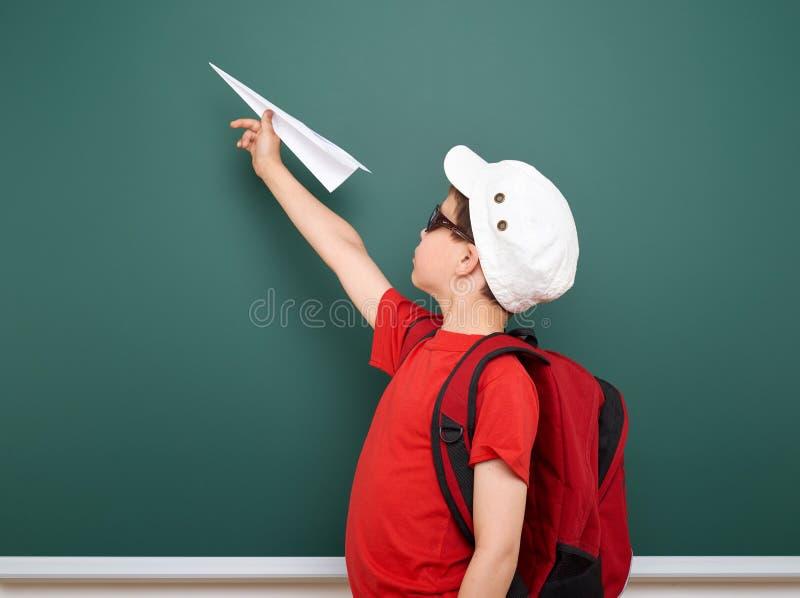 Écolier avec le jeu plat de papier près d'un tableau noir, l'espace vide, concept d'éducation image stock