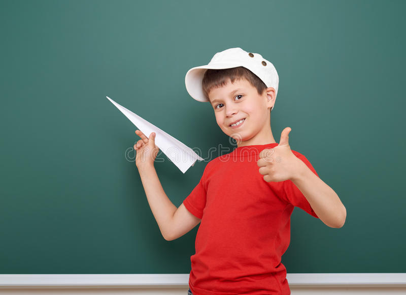 Écolier avec le jeu plat de papier près d'un tableau noir, l'espace vide, concept d'éducation images stock