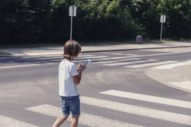 Écolier avec le téléphone sur le passage pour piétons rentrant à la maison photos libres de droits