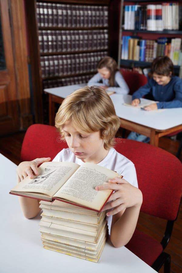 Écolier avec les livres empilés lisant dans la bibliothèque images stock