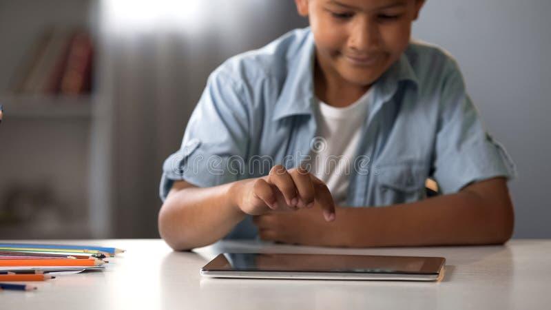 Écolier d'afro-américain observant son exposition éducative préférée sur le comprimé photo stock