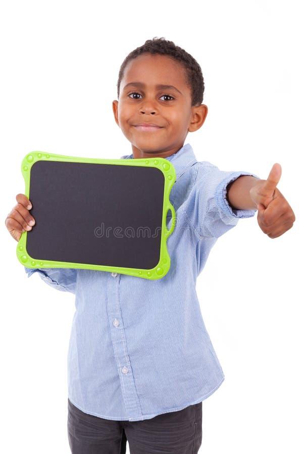 Écolier d'Afro-américain tenant un panneau noir vide - noir photos stock
