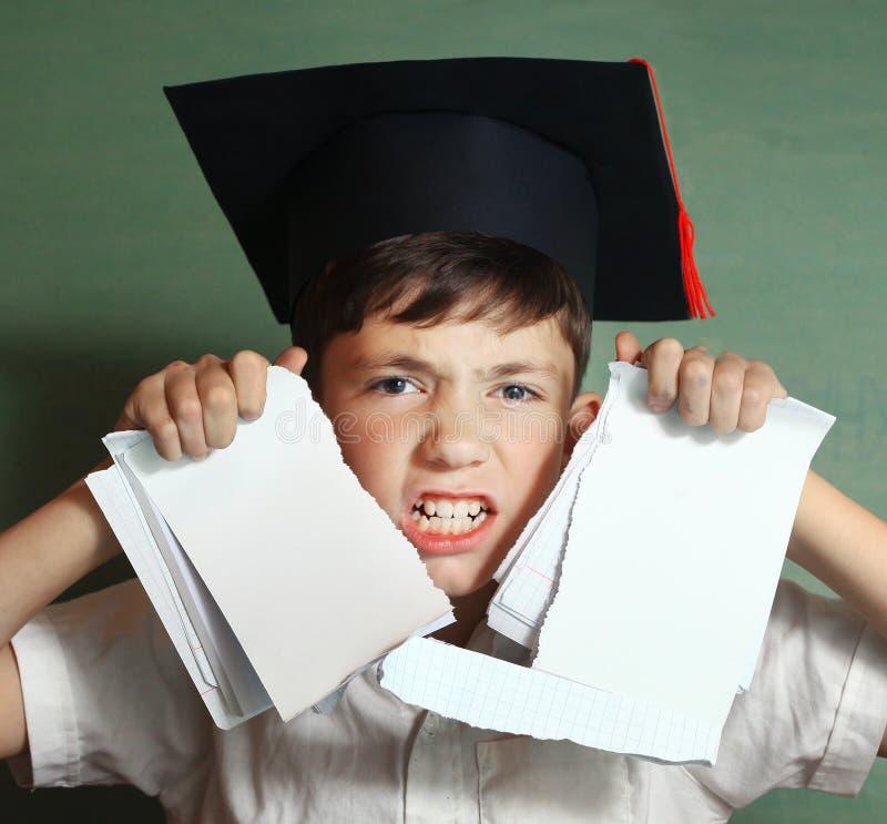 Écolier dans le rebelle de chapeau d'obtention du diplôme contre apprendre dur photographie stock