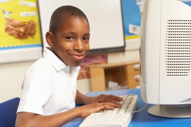 Écolier dans LUI classe utilisant l'ordinateur photo stock
