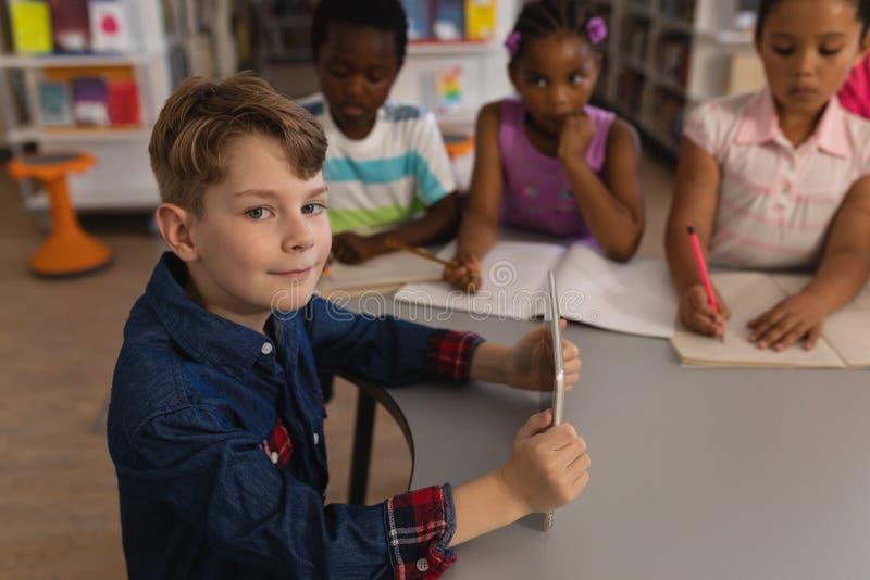 Écolier de sourire tenant le comprimé numérique et regarder la caméra dans la bibliothèque d'école images libres de droits