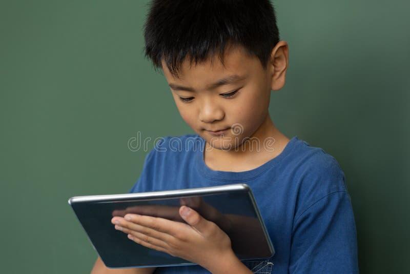 Écolier employant la table numérique contre le greenboard dans une salle de classe photos stock