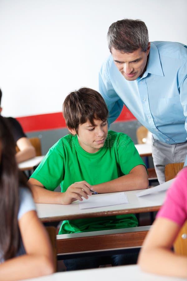 Écolier et professeur Looking At Paper pendant photo stock