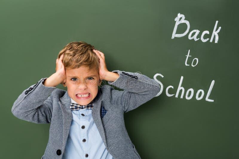 Écolier fâché tenant sa tête images libres de droits