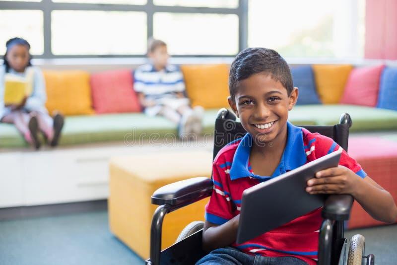 Écolier handicapé sur le fauteuil roulant utilisant le comprimé numérique dans la bibliothèque image libre de droits