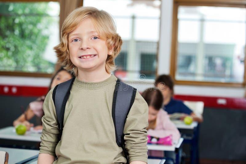 Écolier heureux avec des camarades de classe étudiant dedans photos stock