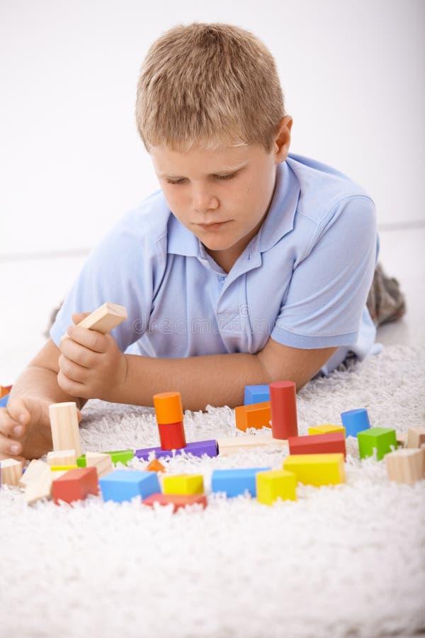 Écolier jouant avec des cubes à la maison photographie stock